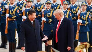 China's President Xi Jinping and US President Donald Trump (L-R front) shake hands during a meeting outside the Great Hall of the People in Beijing in 2017