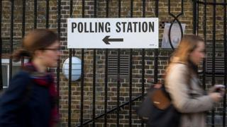 "Women passing a ""polling station"" sign"