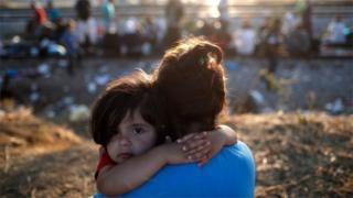 A young Syrian migrant girl is held by her mother
