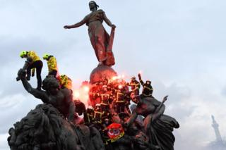 Firefighters brandish flares as they climb on the Statue of Republic Triumph at Nation square in Paris during a demonstration to protest against French government's plan to overhaul the country's retirement system