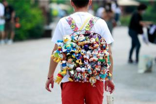 A visitor walks with dolls hanging from the backpack