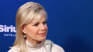 Gretchen Carlson sits in front of a microphone for a radio interview