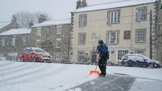 A man clears the roads after heavy snow in Allendale, Northumberland.
