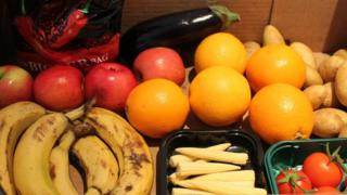 A box of fruit, vegetables and a packet of crisps