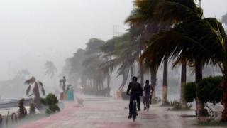 Two men cycle during the passage of Hurricane Newton through La Paz, capital of Baja California Sur