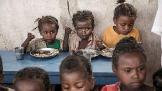 Schoolchildren from Ankileisoke Primary School eat lunch, offered by the World Food Programme's Under-nutrition Prevention Programme, in the Amboasary-South district of southern Madagascar, on December 14, 2018.