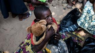 A boy holds his teddy bear as he waits with other Internally Displaced Persons (IDP) for a daily food ration at a camp for people fleeing the conflict in the Kasai province on 7 June 2017 in Kikwit.