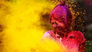 A girl covered in coloured powder closes her eyes