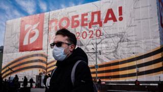 """رجل يرتدي قناع وجه، وسط مخاوف من فيروس """"كوفيد - 19"""" التاجي، يمشي أمام لافتة ضخمة بمناسبة الذكرى 75 المقبلة للانتصار على ألمانيا النازية في الحرب العالمية الثانية"""
