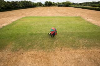 A man poses for a photograph at Priston Cricket Club as he sits on the wicket that has been watered by a hosepipe.