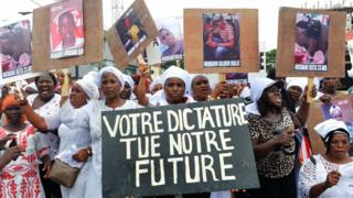 """Guinean women hold placards reading """"Your dictatorship kills our future"""" as they protest against killings of demonstrators and the third term of Guinean President Alpha Conde, demanding also the release of people arrested in Conakry on October 23, 2019. - Hundreds of women opposed to a third term of President Guinean Alpha Condé marched on Wednesday in Conakry, the day after the condemnation of the main initiators of protests that have shaken Guinea for a week and have killed about ten people."""