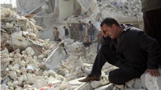 Житель Алеппо на руинах здания