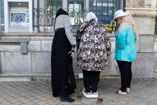 A woman on a weighing scale outside a bank observed by two other women in Tunis, Tunisia - Thursday 30 August 2018