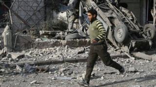 A man runs after an air raid in the besieged town of Douma, Eastern Ghouta, 23 February