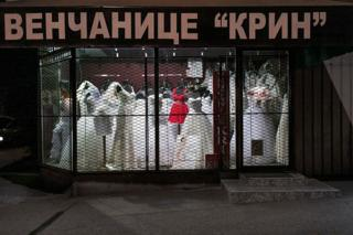 The window of a wedding dress shop lit at night