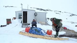 Pobladores en una pequeña cabaña preparan un trineo