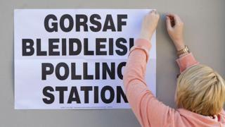 Woman pinning polling station poster up in Welsh language and English