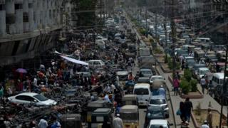 Commuters make their way along a busy street in a market area after the government eased the nationwide lockdown in Karachi on 14 May