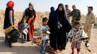 Displaced Iraqi people who fled from Al-Riyadh district arrive to be transported to camps for displaced people, southwest of Kirkuk