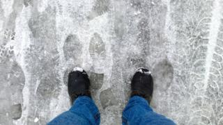 A man's feet standing on ice