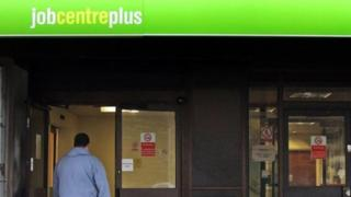 woman with pushchair and man walking into a job centre