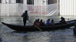 """A boat sails past a writing reading """"Don""""t be selfish, Venice is to be lived"""" during a protest against the increasing number of tourists in Venice, Italy, Saturday, Nov.12. 2016"""