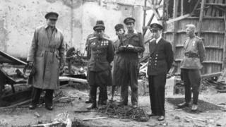 Richard Dimbleby, BBC War Correpondent outside Hitler's underground shelter in Berlin, with the Russian major who is in charge of the Chancellery, and others