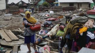 A woman walks among debris in a devastated area after a tsunami hit Sunda Strait in Sumur, Banten