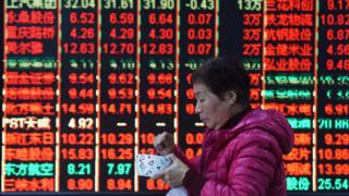 A woman walks part stock market board in China