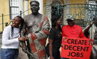 Members of South Africa's trade union take a break from their May Day march to push for better wages to pose with statues in Cape Town on 1 May 2018