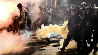 Indonesian police shoot tear gas to disperse protesters during a demonstration outside the Elections Oversight Body (Bawaslu)