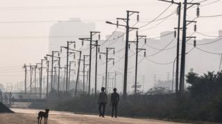 Two Indian men walk past electricity wires near newly built residential towers in Noida, a satellite city of New Delhi.