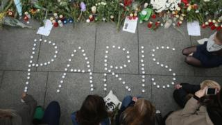 People finish arranging candles into the word 'Paris' next to flowers and messages left at the gate of the French Embassy following the recent terror attacks in Paris on 14 November 2015 in Berlin, Germany.