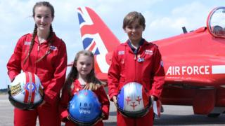 Blue Peter competition winners in front of an RAF aircraft holding helmets with their winning designs.