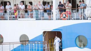 People wait around on the AIDAmira, an Italian registered cruise ship carrying mostly German passengers, as the ship is docked in Cape Town harbour, and is being quarantined due to several suspected COVID-19 cases on board, on March 18, 2020, in Cape Town.