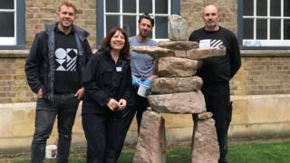 Conservators and installations staff with the newly-restored sculpture