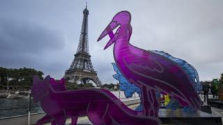 Sculptures in animal shapes adorn the deck of a barge, as part of an art installation entitled Climate Noah's Ark by artist Gad Weil, near the Eiffel Tower, in Paris, France (September 2015)