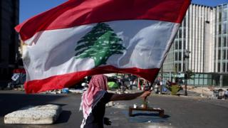 An anti-government protester holds up a Lebanese flag at a camp in Beirut (30 October 2019)