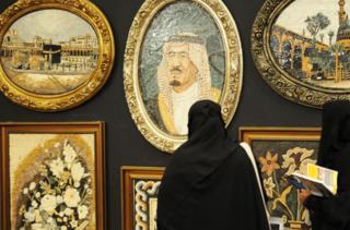 امرأة سعودية تنظر إلى لوحة للملك السعودي