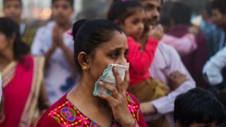 امرأة هندية تغطي أنفها بمنديل بسبب الأتربة والتلوث