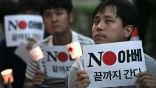 """معترضان در کره جنوبی پلاکاردهایی با مضمون """"نه آبه"""" در اعتراض به تصمیم ژاپن در دست دارند"""
