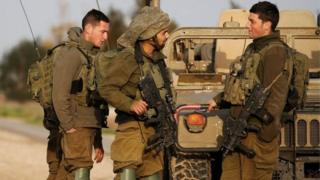 Israeli soldiers stands near a military jeep next to the border fence with the southern Gaza Strip near Kibbutz Nirim,