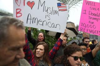 """Manifestantes protestando contra la orden de """"escrutinio extremo"""" de Trump."""