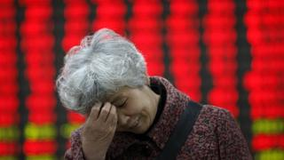 Chinese lady in front of stock price board