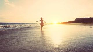 Happy little girl running inside water on the beach at sunset -