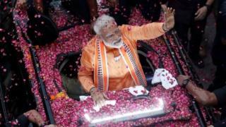 Prime Minister Narendra Modi waves supporters for oad show in Varanasi.