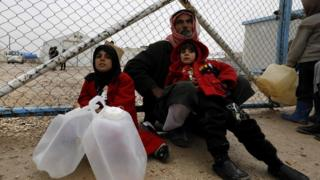 File photo showing a displaced Syrian family wait to fill up water containers at a camp for displaced people in al-Hol, Hassakeh province (17 December 2018)