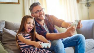 Girl and dad using consoles
