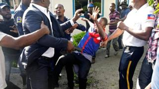 Haitian Senator Willot Joseph holds a gun as he pushes an opposition supporter in Port-au-Prince, Haiti