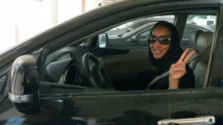 "Saudi Arabian activist Manal Al Sharif, who now lives in Dubai, flashes the sign for victory as she drives her car in the Gulf Emirate city on October 22, 2013, in solidarity with Saudi women preparing to take to the wheel on October 26, defying the Saudi authorities, to campaign women""s right to drive in Saudi Arabia."